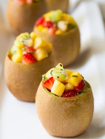Tropical Fruit Salad in Kiwi Cups on ASpicyPerspective.com #fruitsalad #kiwi