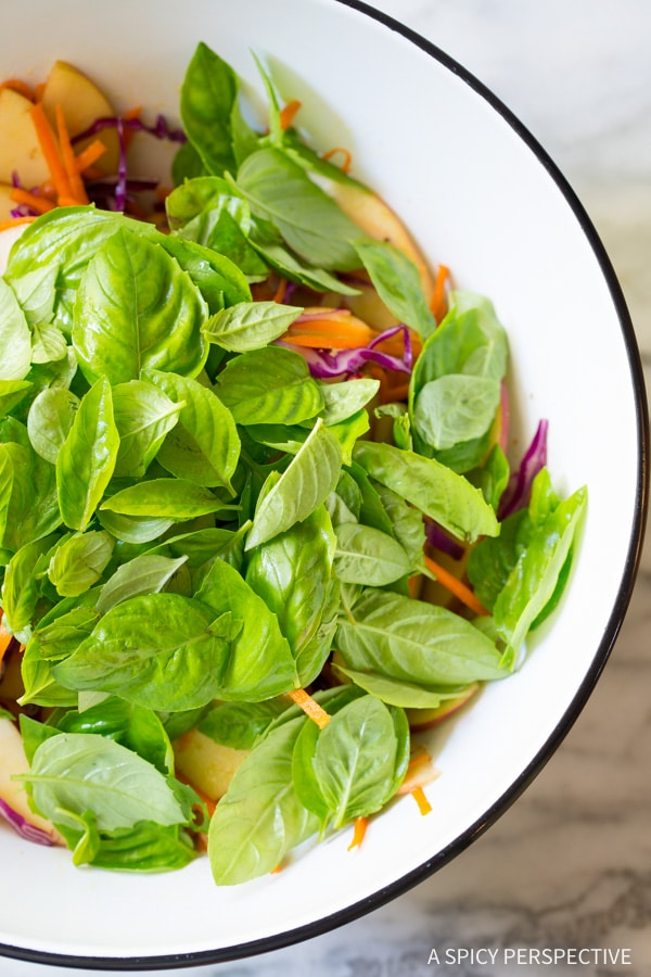 Zesty Apple Slaw Salad with Fresh Basil Leaves and Sunflower Seeds on ASpicyPerspective.com