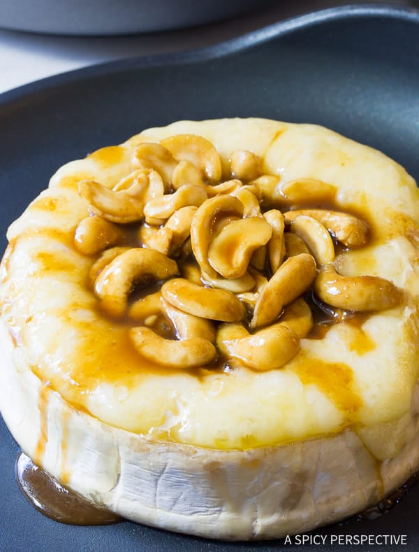 Easy Baked Brie with Cashews and Bourbon Brown Sugar Glaze Recipe on ASpicyPerspective.com. #holidays #christmas