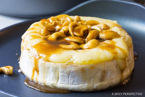 Crazy over this Easy Baked Brie with Cashews and Bourbon Brown Sugar Glaze Recipe on ASpicyPerspective.com. #holidays #christmas