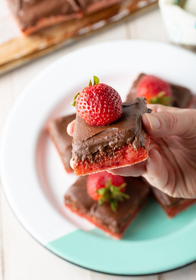 fresh strawberries on brownies with thick fudge icing