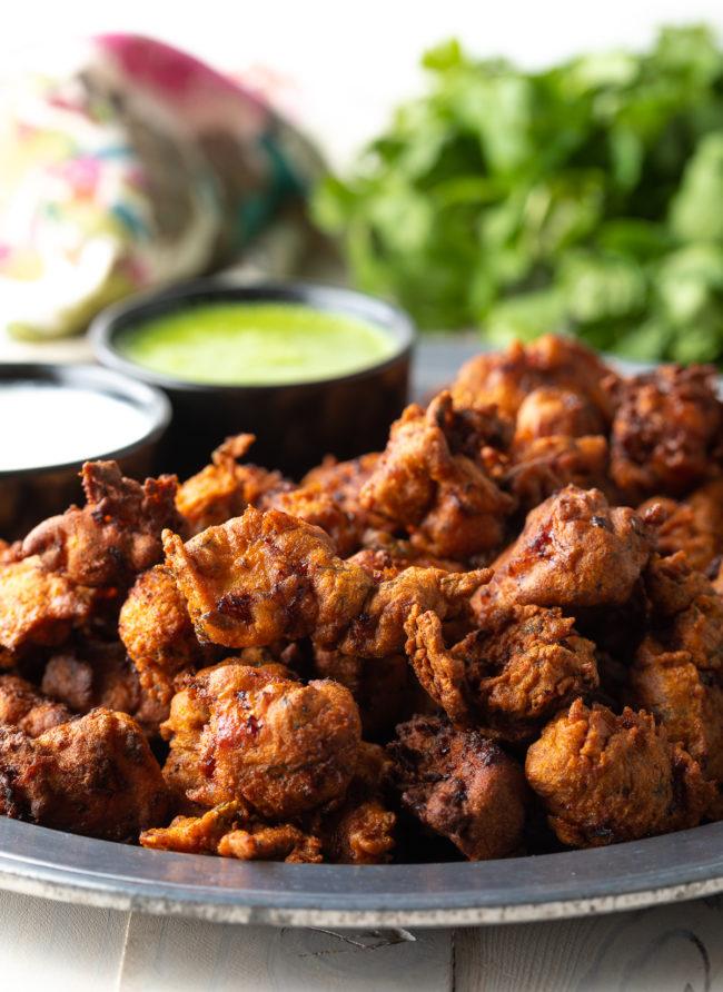 Easy Chicken Pakora Recipe served with Indian Green Chutney and Raita Yogurt Sauce!