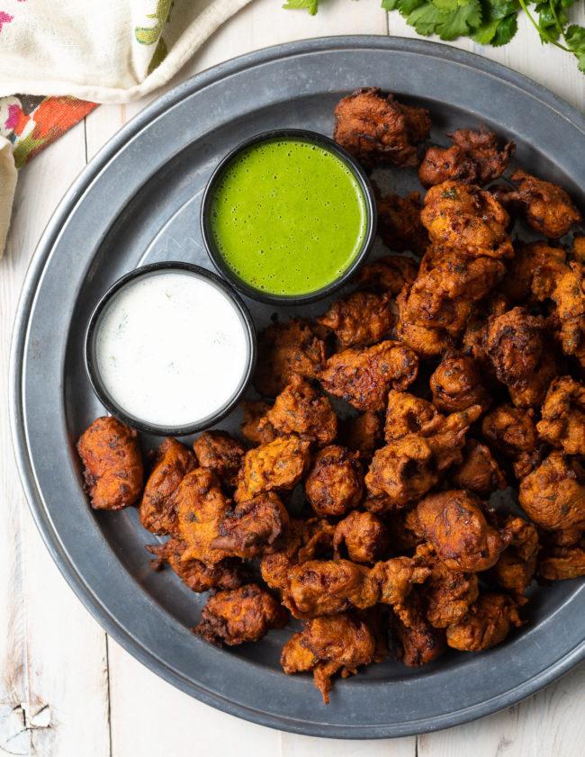 Indian Chicken Recipe on a platter with green chutney and raita yogurt sauce