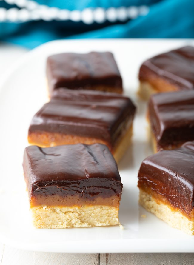 layers of shortbread cookie, luscious caramel and peanut butter fudge, and chocolate ganache