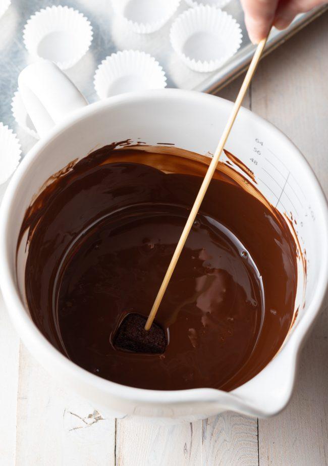 dipping mini cake in chocolate