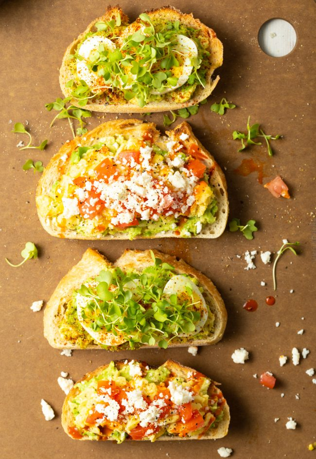 pieces of toast topped with avocado and goodies