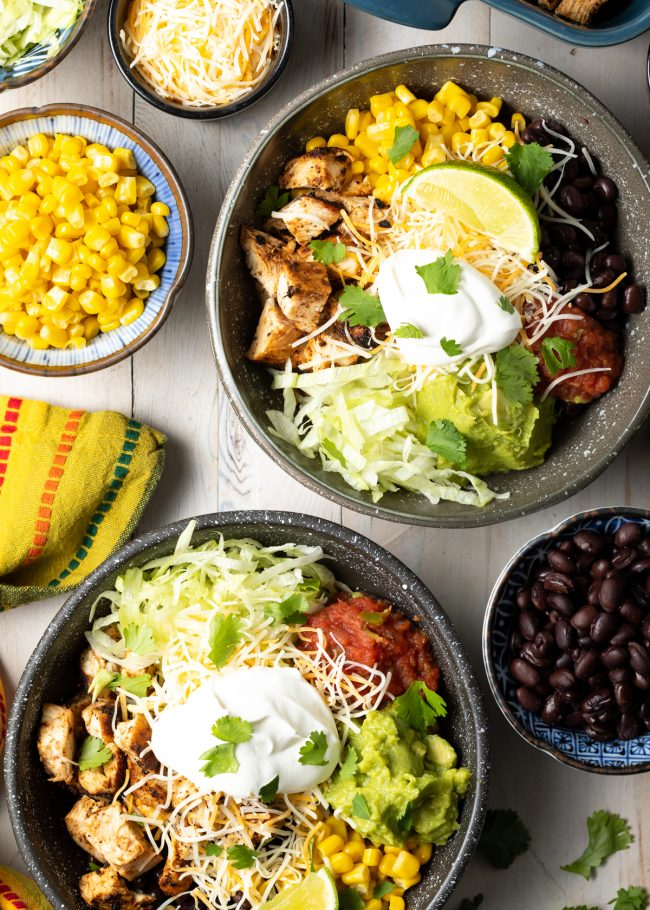 grilled chipotle chicken burrito bowls with beans, corn, southwestern toppings