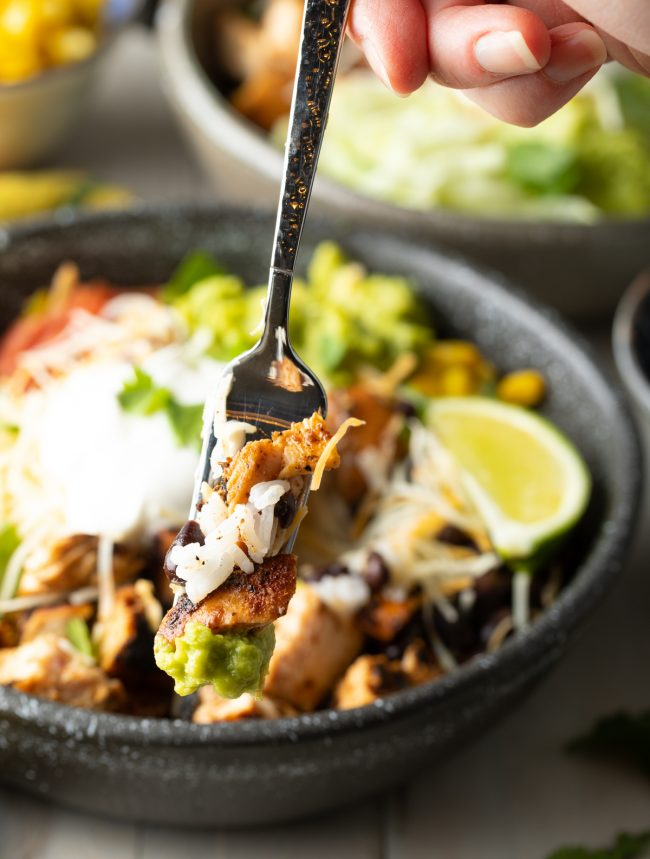 bite of burrito bowl with rice, chicken, and beans