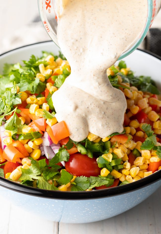pouring dressing onto veggies and gluten free noodles