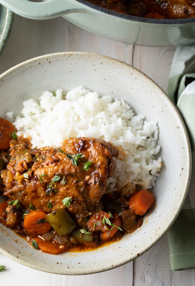 Jamaican brown stew chicken with rice in a bowl