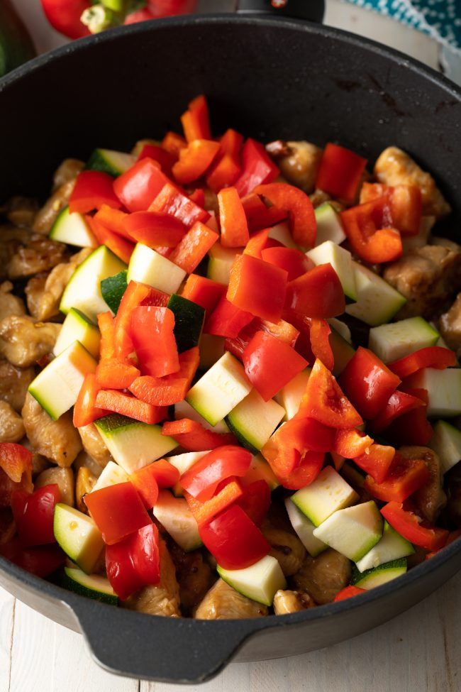 sauteeing fresh chopped veggies with chicken in a skillet