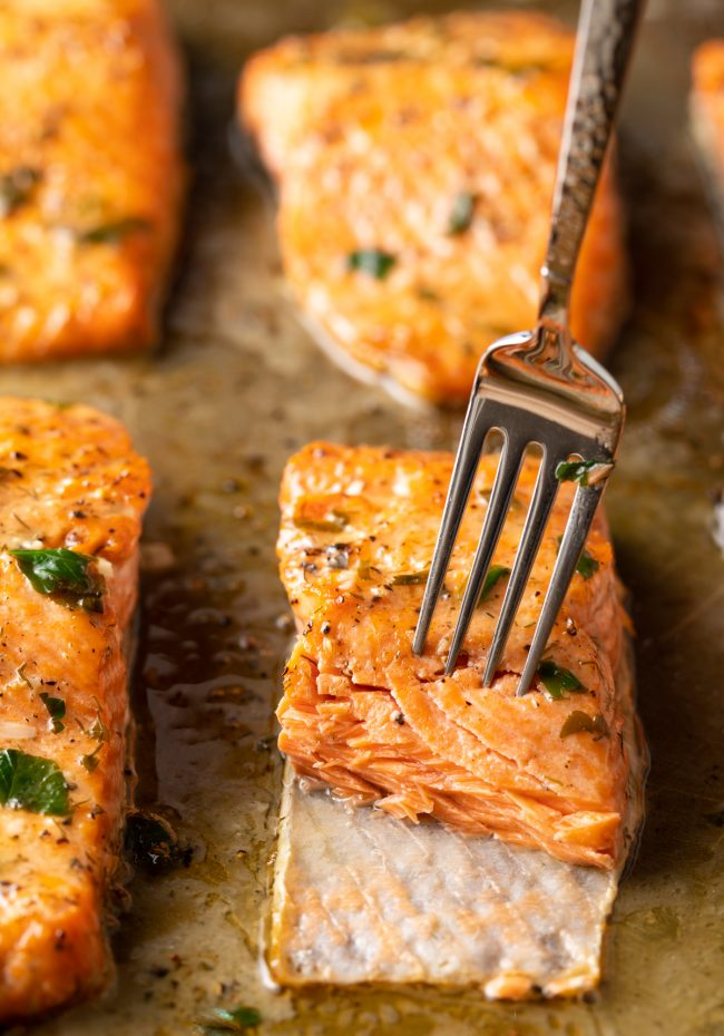 fork flaking broiled salmon with garlic herb butter