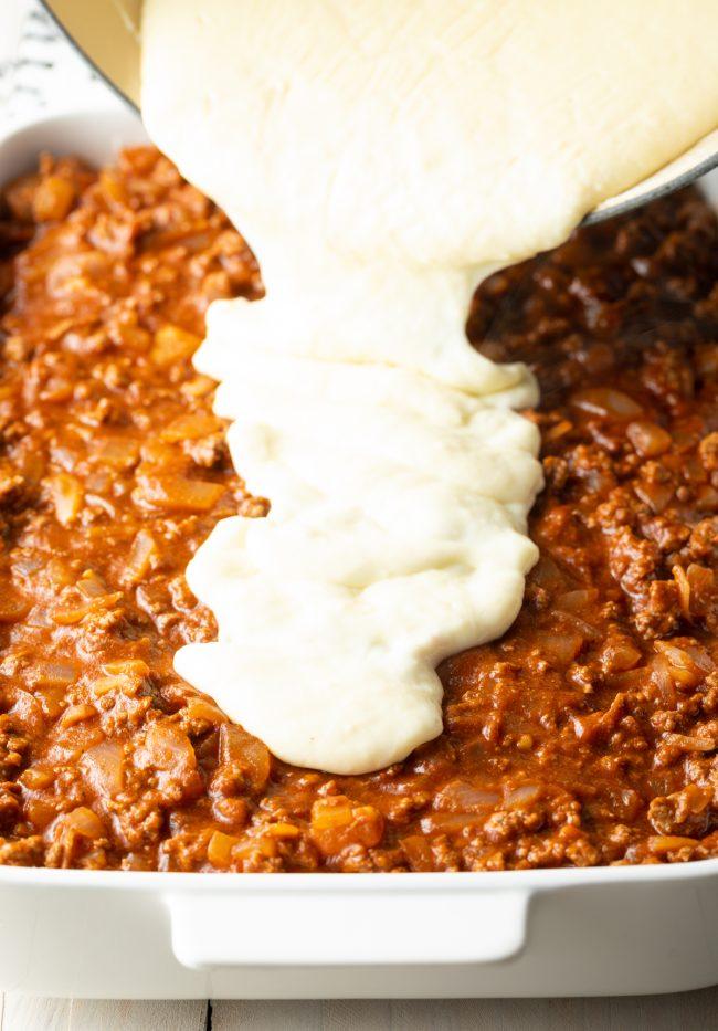 pouring bechamel over the Greek lasagna meat sauce