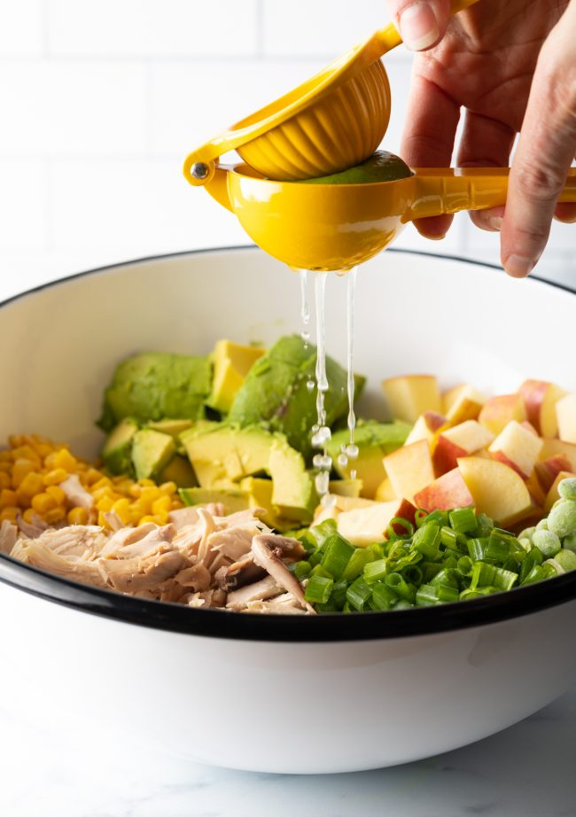 squeezing lime juice onto the ingredients