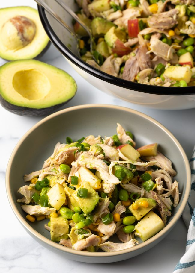 chopped chicken, avocados, apples, kernels of corn, edamame, scallions in a bowl
