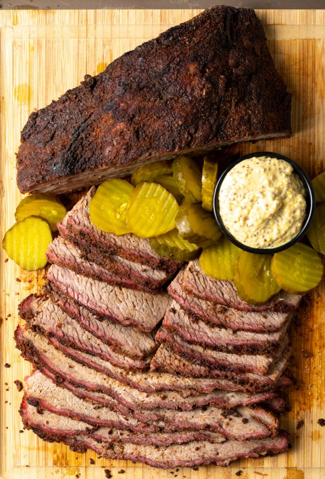 slices of smoked beef brisket on a board with pickles and mustard