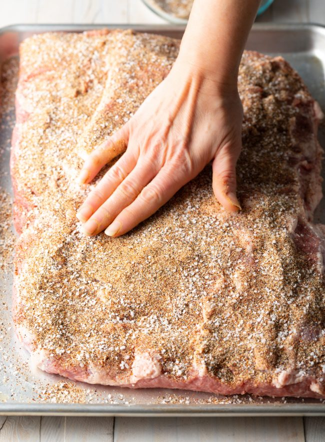rubbing the dry brine spices onto the meat