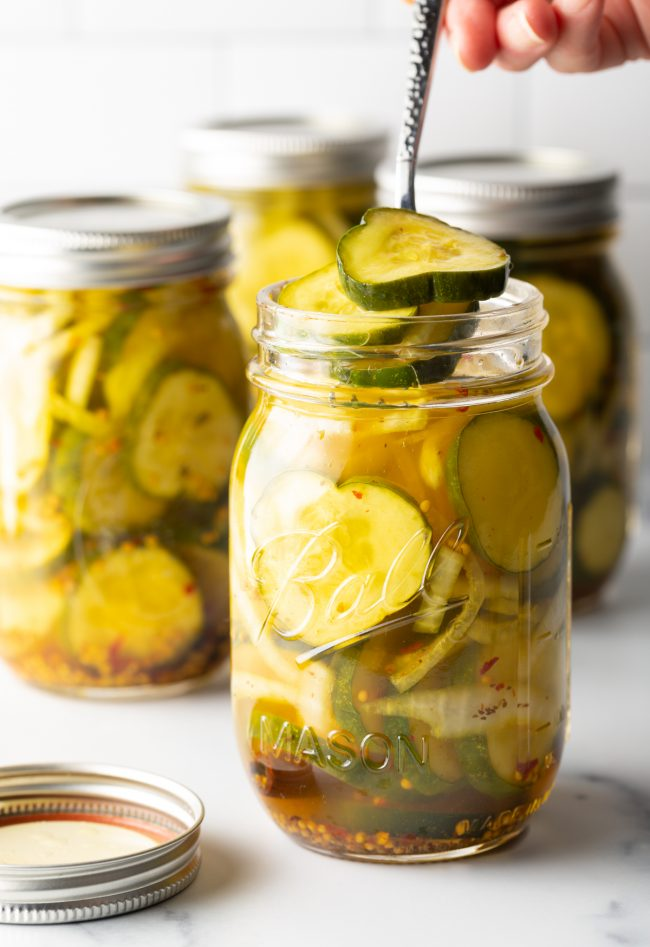 using a fork to remove bread and butter pickle slices from jars