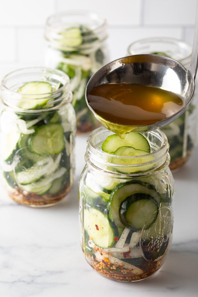 pouring the hot pickling liquid into the jars filled with cucumbers, onions, and spices