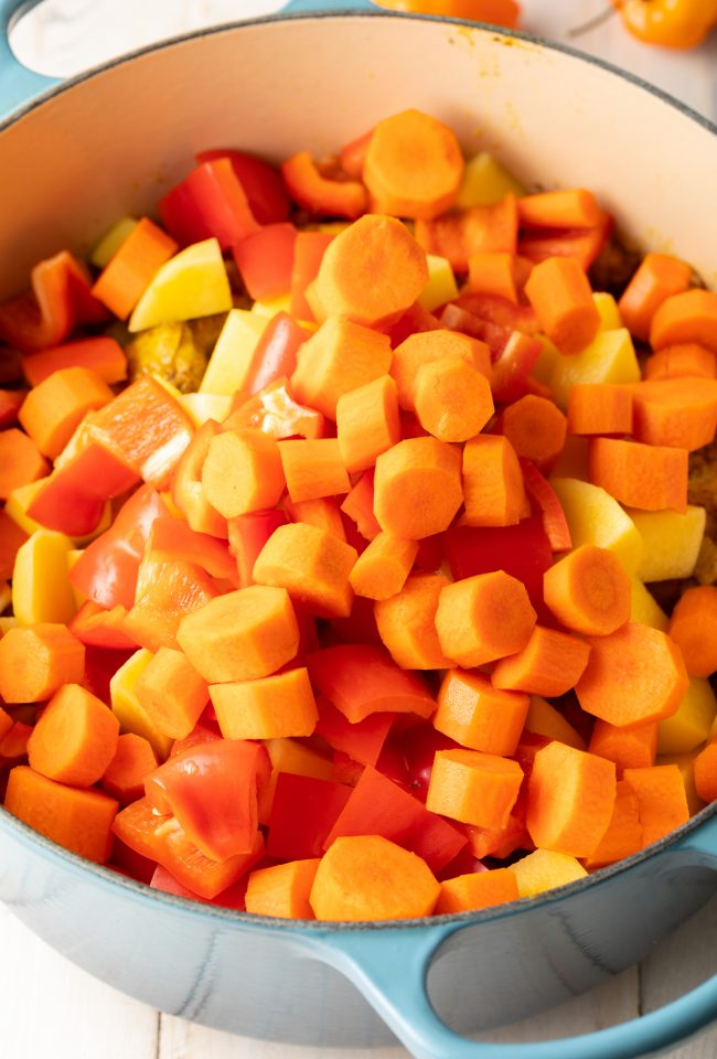 chopped carrots, peppers, and potatoes added to a pot
