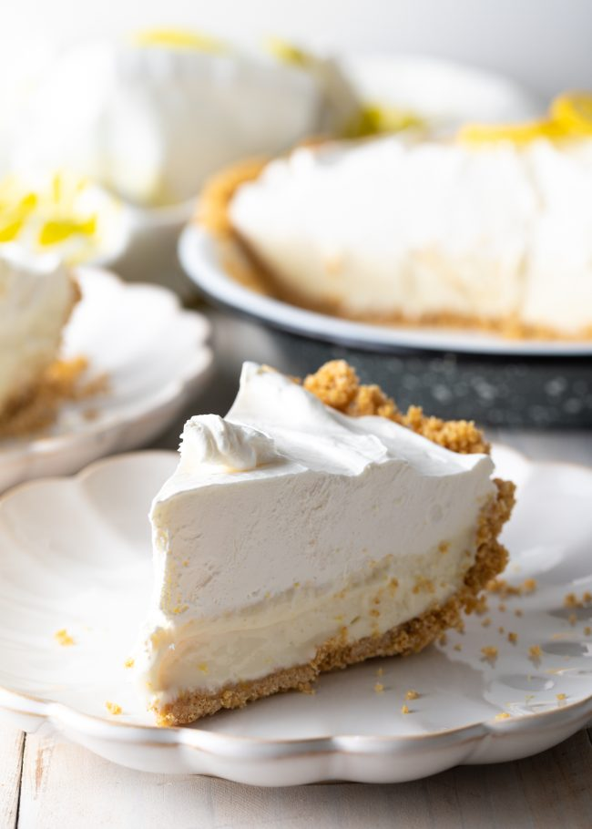 slice of lemon icebox pie on a plate with pie in the background
