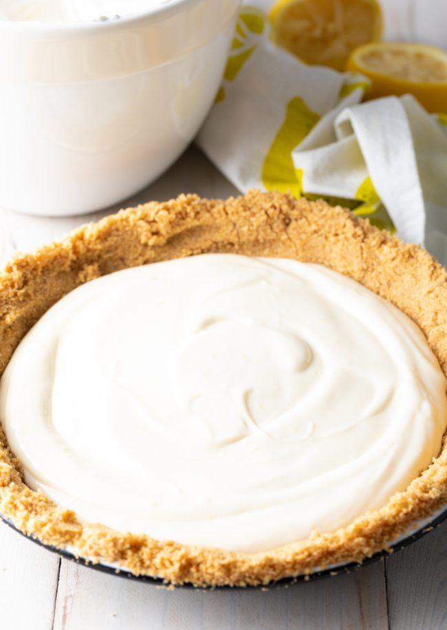creamy lemon filling scooped into graham cracker crust