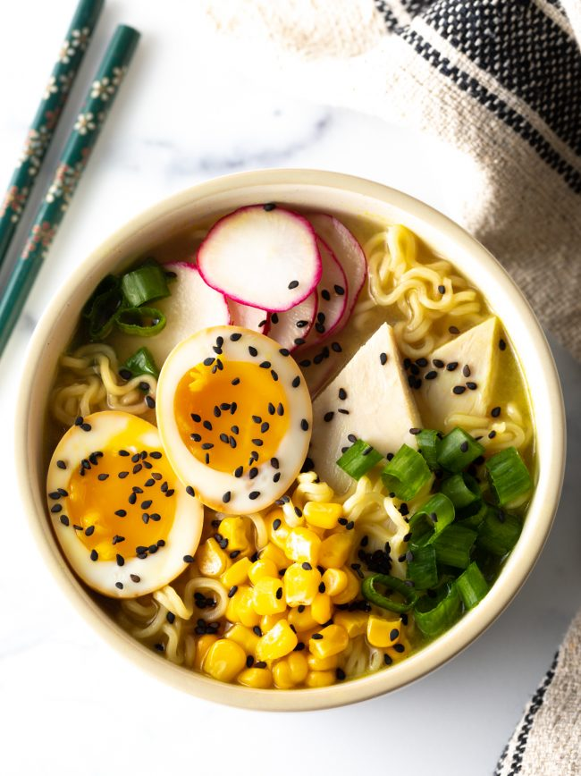 ramen bowl loaded with noodles, tofu, eggs, corn, and radishes