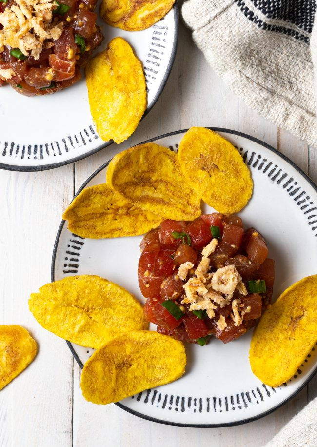 two plates of tuna tartare garnished with onions and served with plantain chips