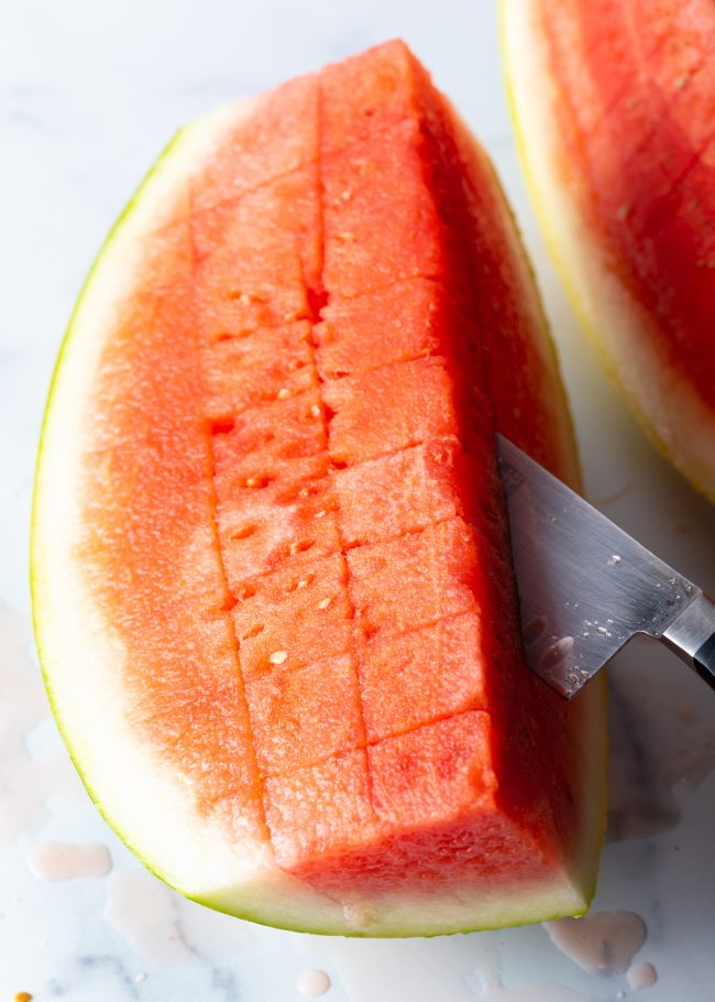 using a knife to cut a watermelon into cubes