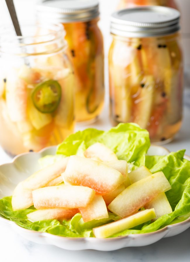 slices of pickled watermelon rind on a plate with lettuce