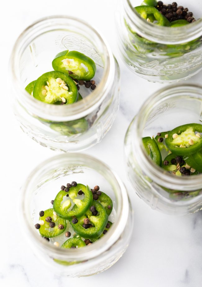 jalapeno slices and peppercorns in jars
