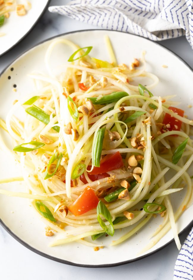 a plate of som tum green papaya salad with tomatoes, beans, and peanuts