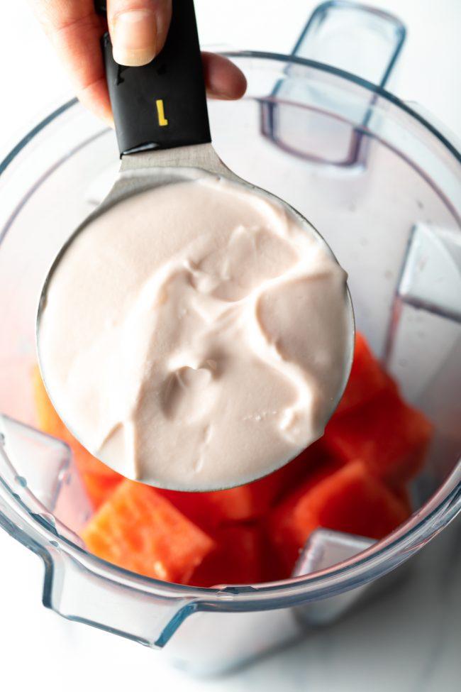 adding yogurt to the blender