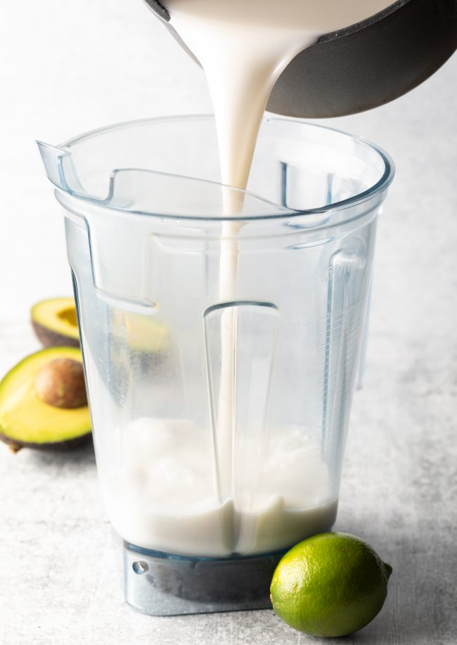 pouring coconut milk and sugar into a blender