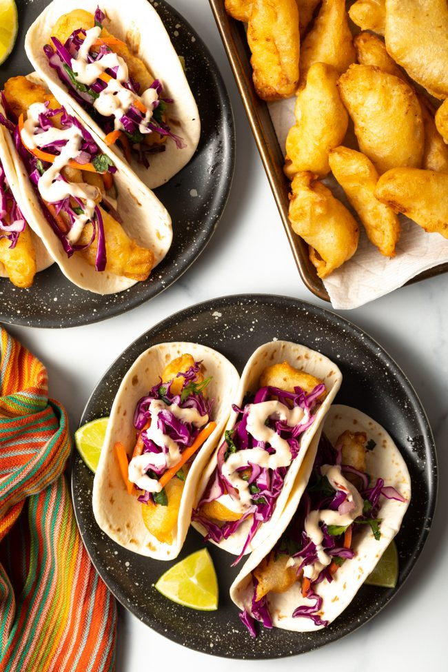plates of fried fish baja tacos with shredded cabbage slaw and fish taco sauce