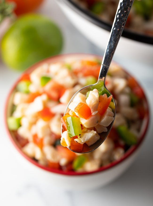 spoonful of conch salad with peppers and tomatoes