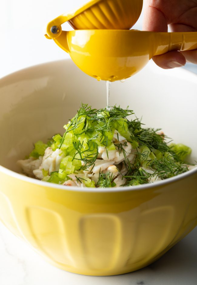 adding lemon juice, chopped celery and dill to a bowl