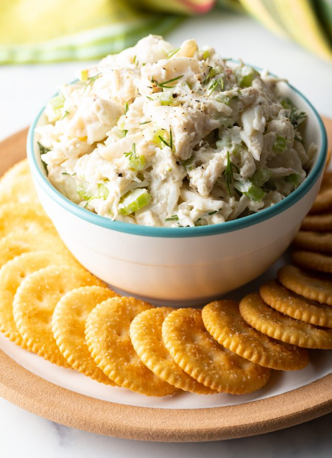 a bowl of seafood salad with chopped celery and dill with crackers