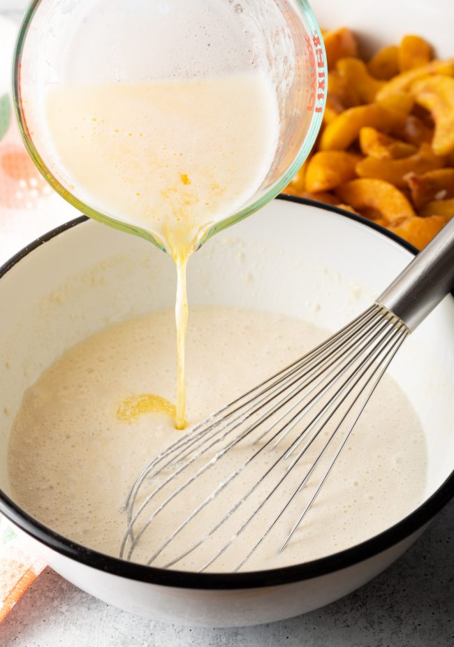 whisking melted butter into the batter