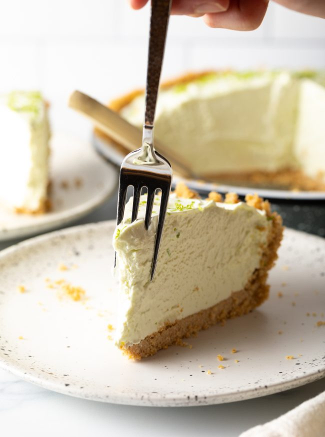 taking a bite of a slice of frozen key lime pie