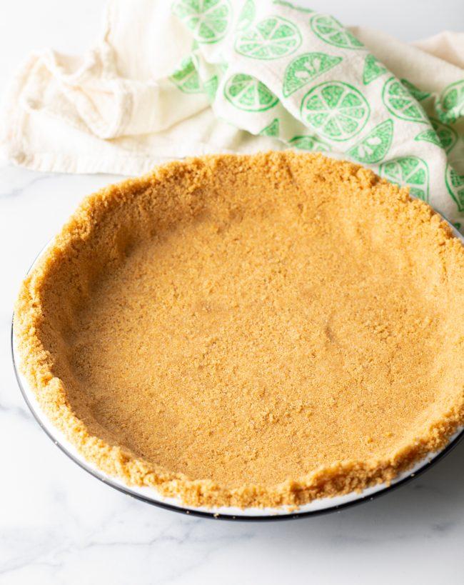 pressed graham cracker crust mixture in a pie plate
