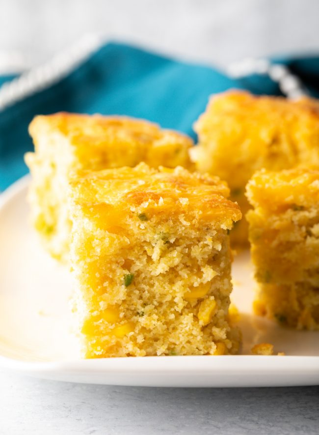 cut squares of homemade cheesy cornbread with jalapenos