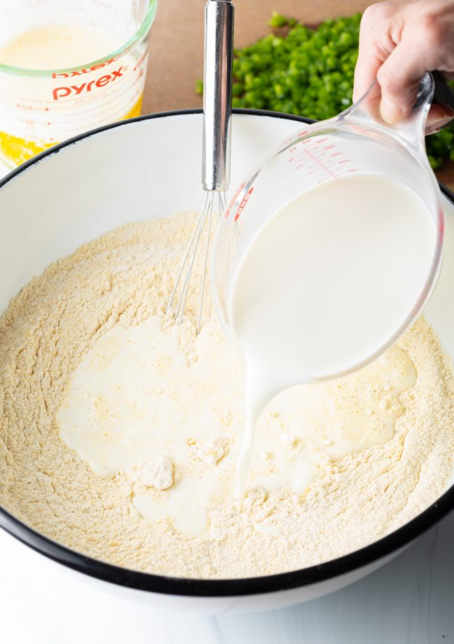 pouring buttermilk into a bowl with baking mix
