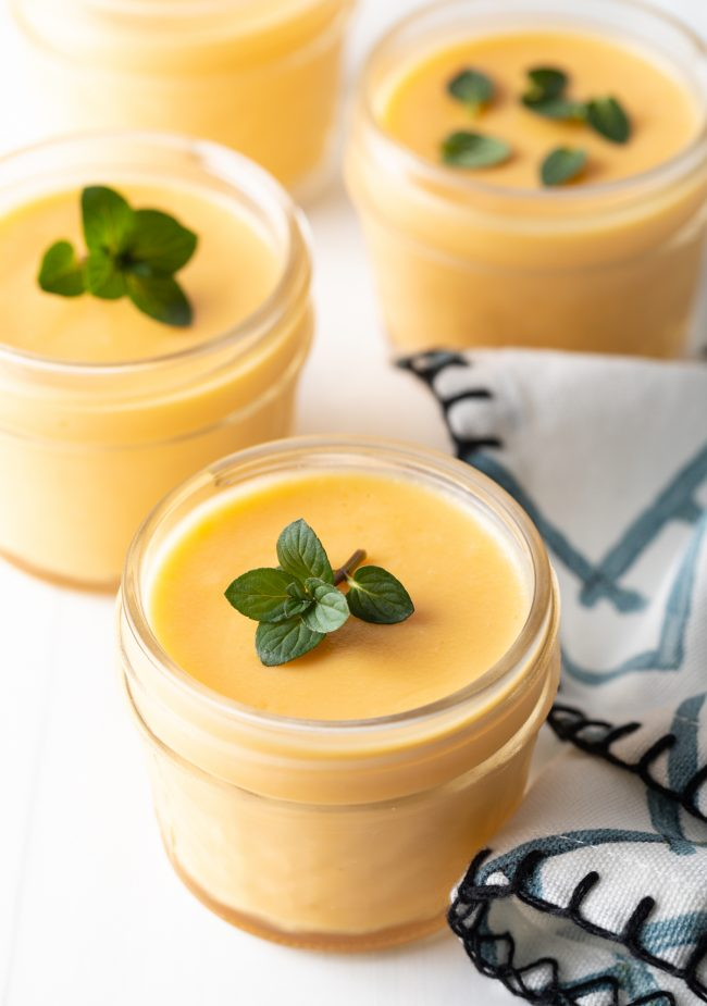 finished Chinese dessert of pudding with mango and sprig of fresh mint to garnish