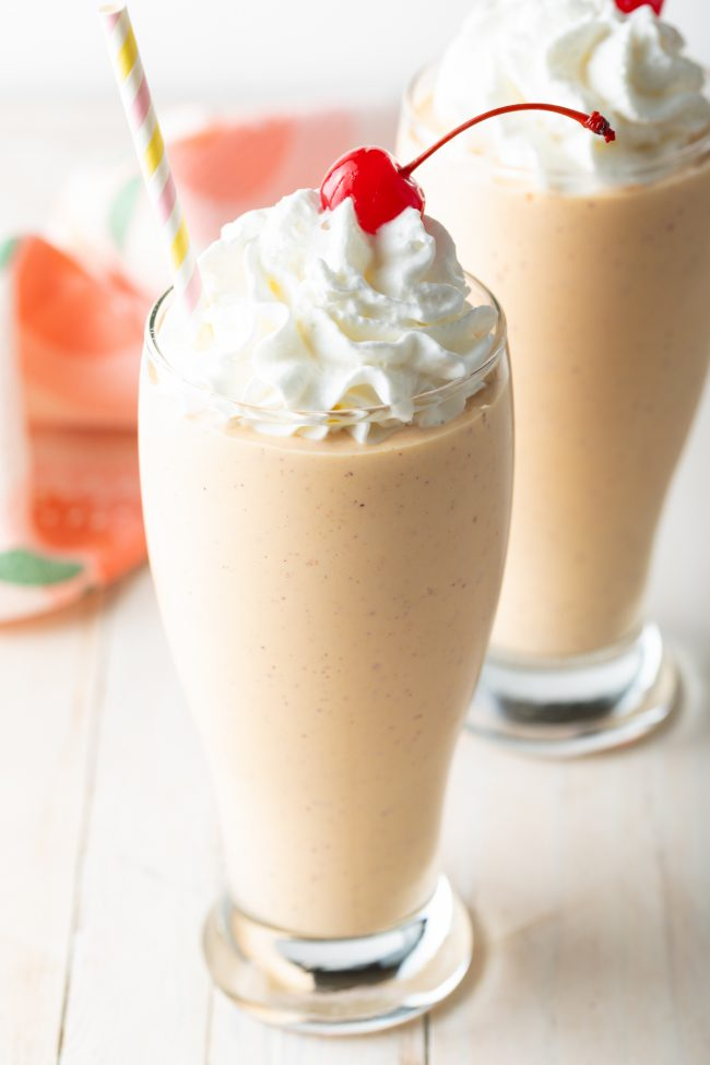tall glasses of homemade peach milkshakes topped with whipped cream and cherries
