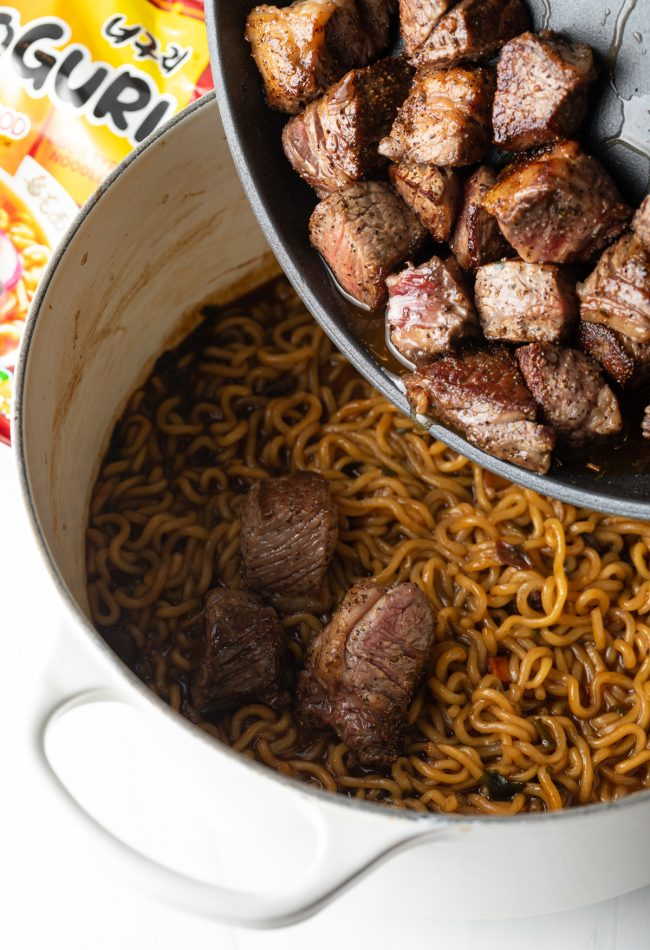adding seared ribeye to the large pot with cooked sauced noodles