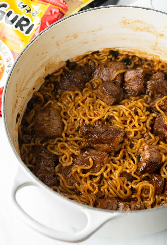 large saucepot with cooked ramen and udon noodles, seared steak, and sauce