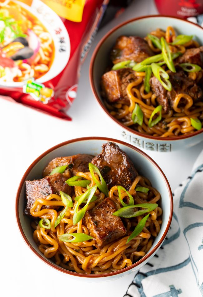 overhead view of two bowls with Korean spicy ramen noodles, steak, and fresh scallions