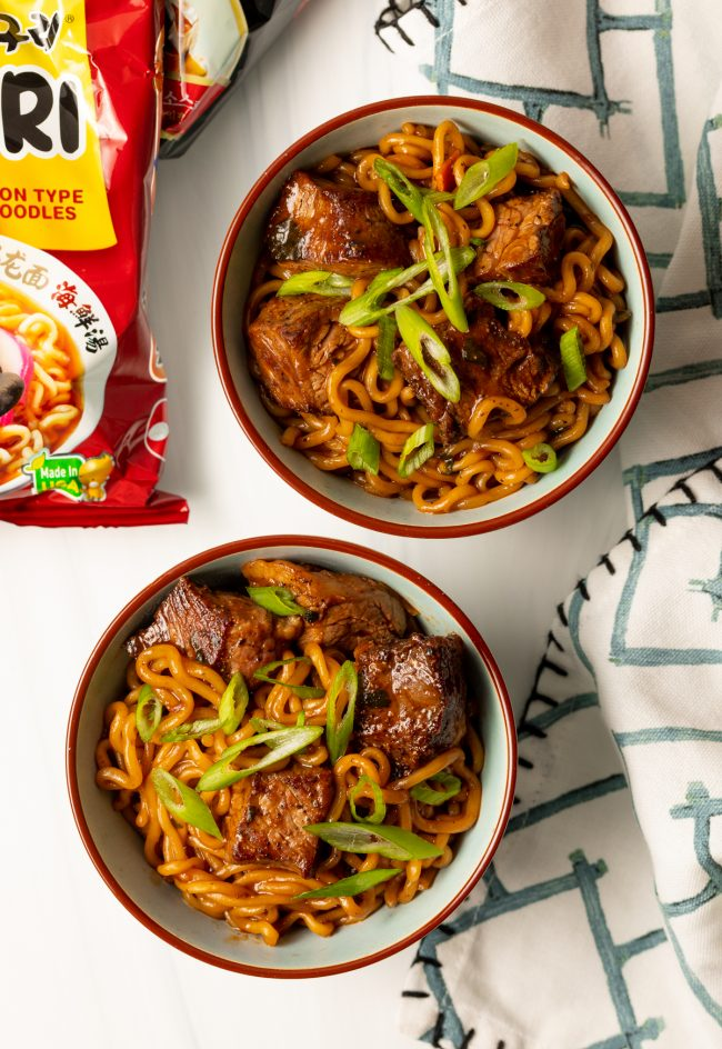 overhead view of two bowls with ram don spicy Korean noodles and scallions