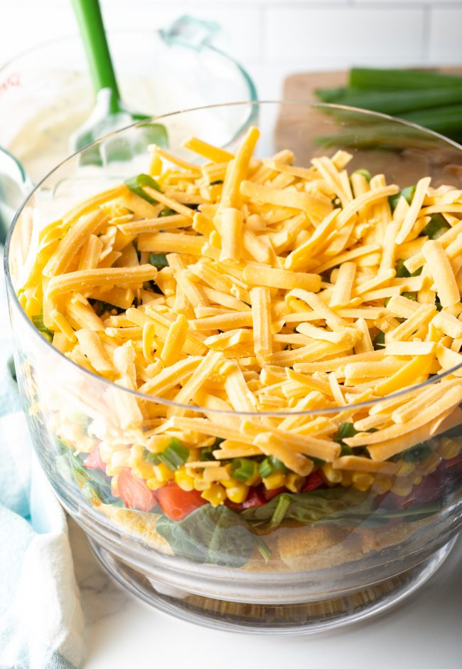 adding a layer of shredded cheddar cheese to the salad